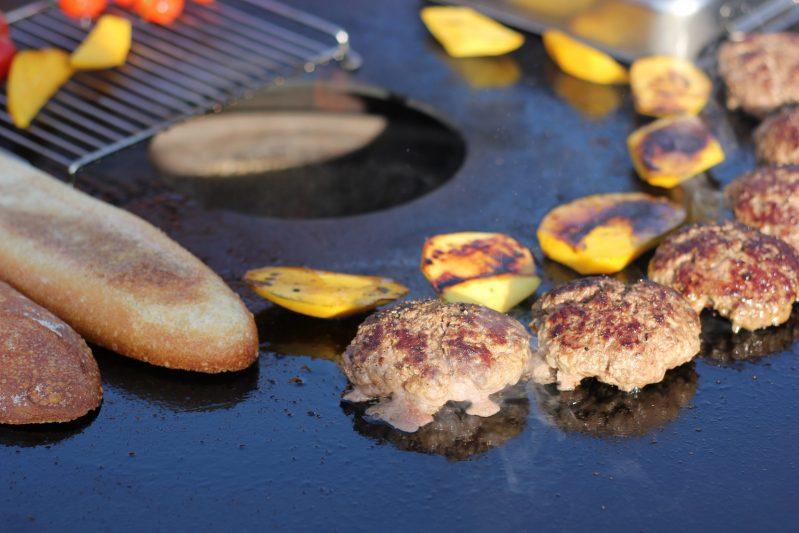 Burger-Pattys und Zutaten werden auf der Platte angegrillt